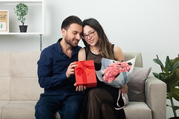 Uśmiechnięty przystojny mężczyzna daje pudełko zadowolonej ładnej młodej kobiecie w okularach trzymającej bukiet kwiatów siedzącej na kanapie w salonie