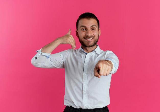 Uśmiechnięty przystojny mężczyzna gesty nazywają mnie ręką znak wskazujący na białym tle na różowej ścianie
