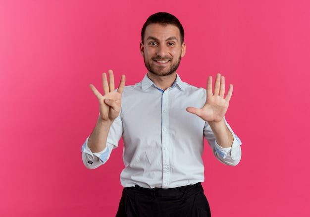 Uśmiechnięty przystojny mężczyzna gestykuluje dziewięć rękami odizolowanymi na różowej ścianie
