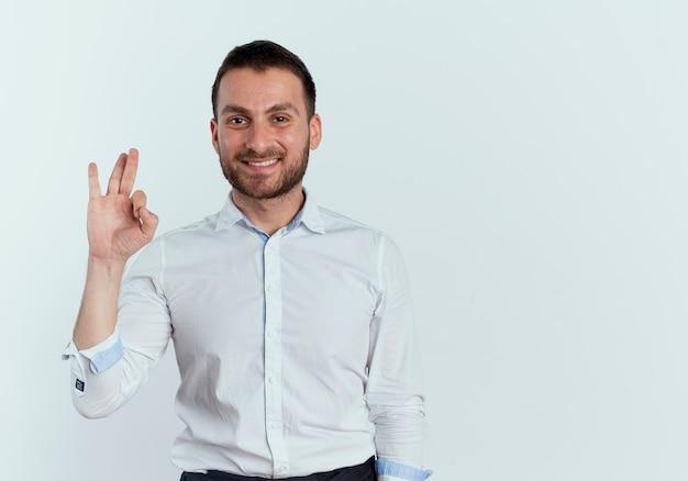 Uśmiechnięty przystojny mężczyzna gestykuluje ok ręka znak na białym tle na białej ścianie