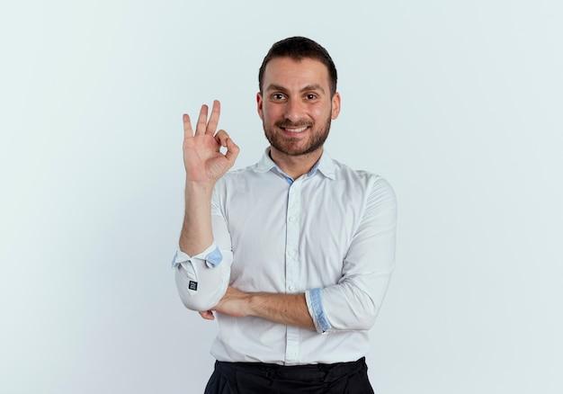 Uśmiechnięty przystojny mężczyzna gestykuluje ok ręka znak patrząc na białym tle na białej ścianie