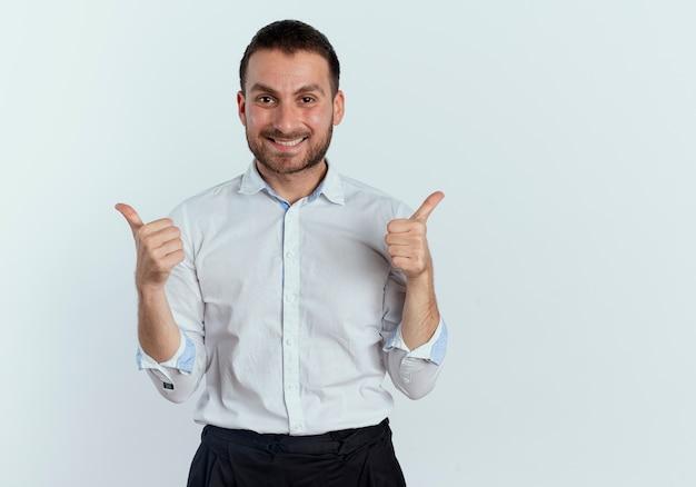 Uśmiechnięty przystojny mężczyzna kciuki w górę dwiema rękami na białym tle na białej ścianie