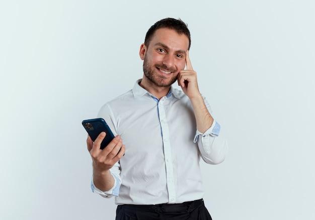 Uśmiechnięty przystojny mężczyzna kładzie palec na świątyni trzymając telefon na białym tle na białej ścianie