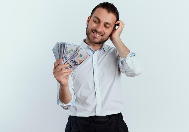 Uśmiechnięty przystojny mężczyzna kładzie rękę na głowie patrząc na pieniądze na białym tle na białej ścianie