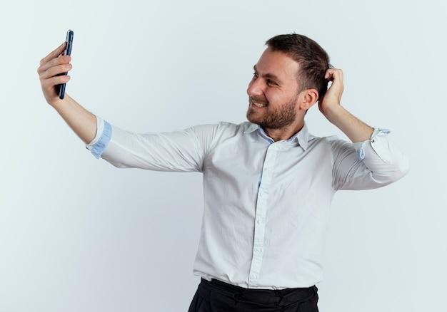 Uśmiechnięty przystojny mężczyzna kładzie rękę na głowie za patrząc na telefon na białym tle na białej ścianie