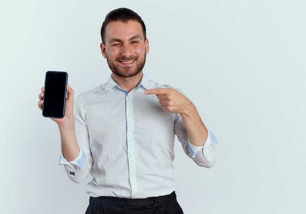 Uśmiechnięty przystojny mężczyzna mruga oczami, trzymając i wskazując na telefon na białym tle na białej ścianie
