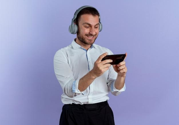 Uśmiechnięty przystojny mężczyzna na słuchawkach trzyma i patrzy na telefon na białym tle na fioletowej ścianie