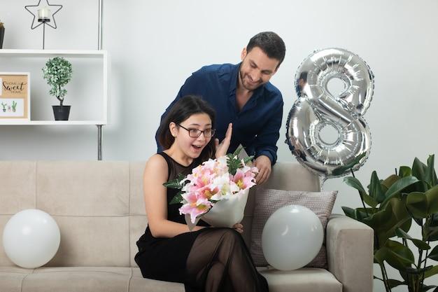 Uśmiechnięty przystojny mężczyzna patrzący na podekscytowaną ładną młodą kobietę w okularach optycznych trzymający bukiet kwiatów siedzący na kanapie w salonie w marcowy międzynarodowy dzień kobiet
