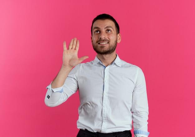 Uśmiechnięty przystojny mężczyzna podnosi rękę patrząc w górę na białym tle na różowej ścianie