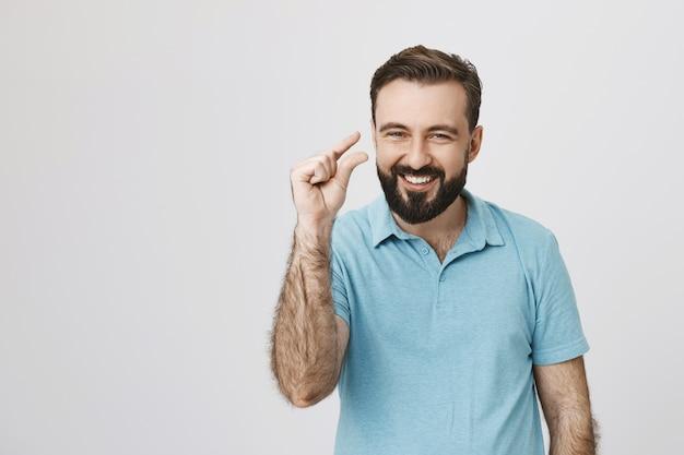 Uśmiechnięty przystojny mężczyzna pokazujący coś małego lub małego