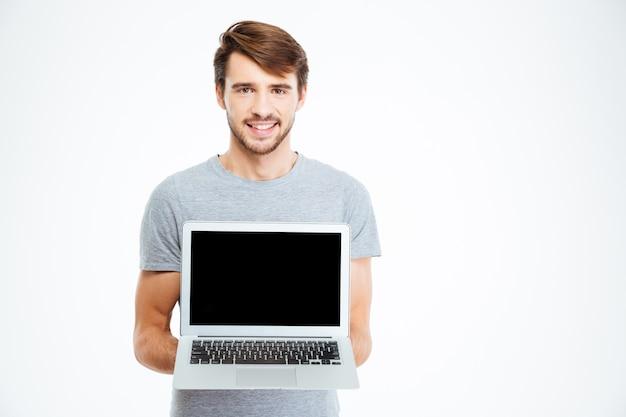 Uśmiechnięty przystojny mężczyzna pokazujący pusty ekran laptopa na białym tle