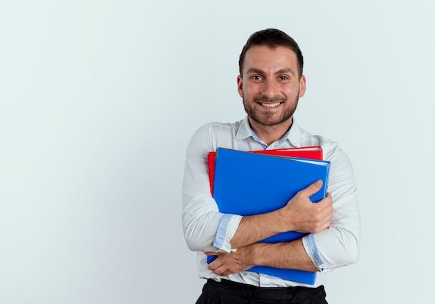 Uśmiechnięty przystojny mężczyzna posiada foldery plików na białym tle na białej ścianie