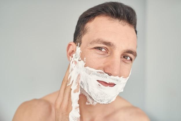 Uśmiechnięty przystojny mężczyzna przygotowujący się do golenia włosia podczas nakładania pianki do golenia na twarz
