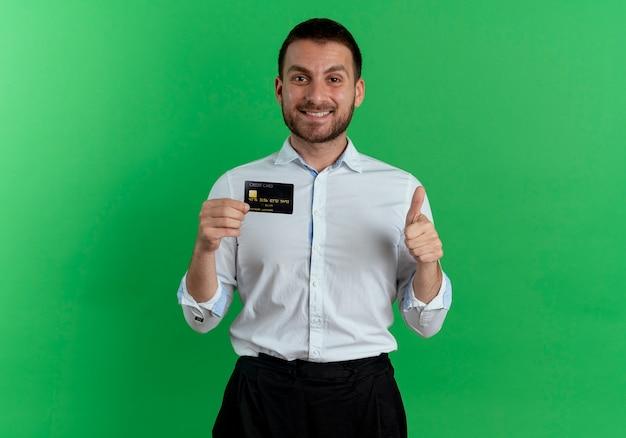 Uśmiechnięty przystojny mężczyzna trzyma kartę kredytową i kciuki do góry na białym tle na zielonej ścianie