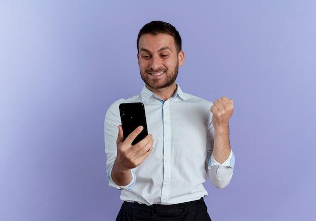 Uśmiechnięty przystojny mężczyzna trzyma pięść i patrzy na telefon na białym tle na fioletowej ścianie