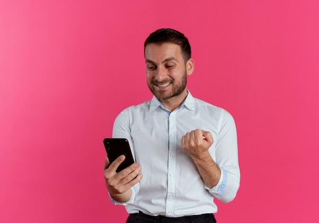 Uśmiechnięty przystojny mężczyzna trzyma pięść trzymając i patrząc na telefon na białym tle na różowej ścianie