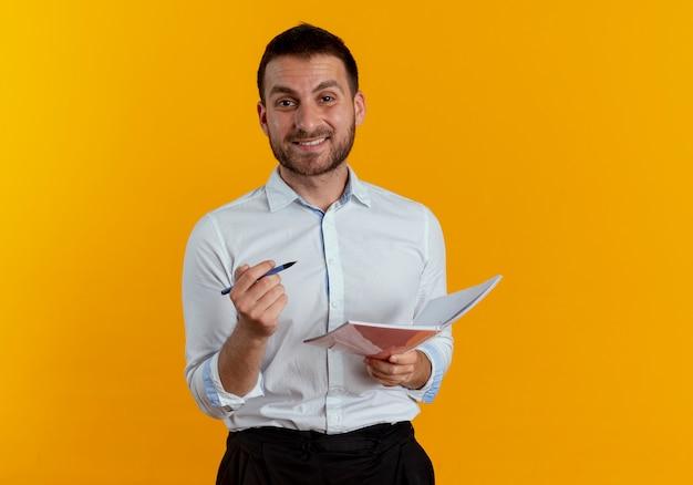 Uśmiechnięty przystojny mężczyzna trzyma pióro i notatnik na białym tle na pomarańczowej ścianie
