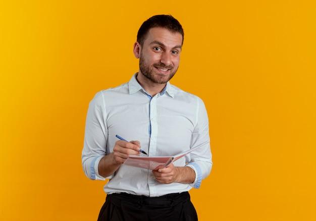 Uśmiechnięty przystojny mężczyzna trzyma pióro i notatnik patrząc na białym tle na pomarańczowej ścianie