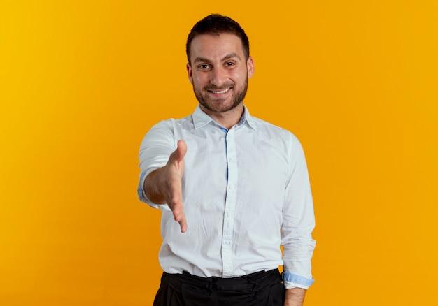 Uśmiechnięty przystojny mężczyzna trzyma rękę na białym tle na pomarańczowej ścianie
