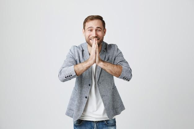 Uśmiechnięty przystojny mężczyzna trzyma się za ręce w modlitwie, prosząc o pomoc lub dziękując
