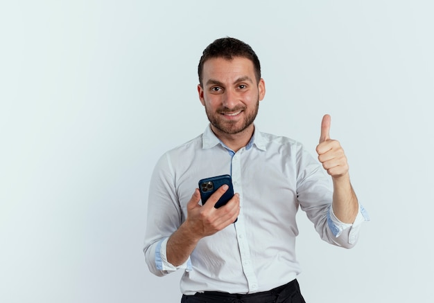 Uśmiechnięty przystojny mężczyzna trzyma telefon i kciuki do góry patrząc na białym tle na białej ścianie