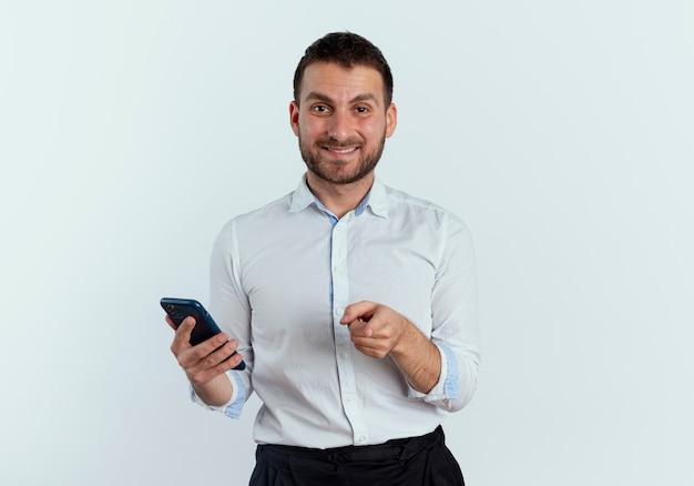 Uśmiechnięty przystojny mężczyzna trzyma telefon i punkty na białym tle na białej ścianie