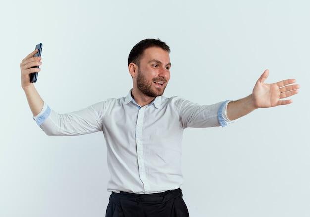 Uśmiechnięty przystojny mężczyzna trzyma telefon i wskazuje na bok ręką na białym tle na białej ścianie