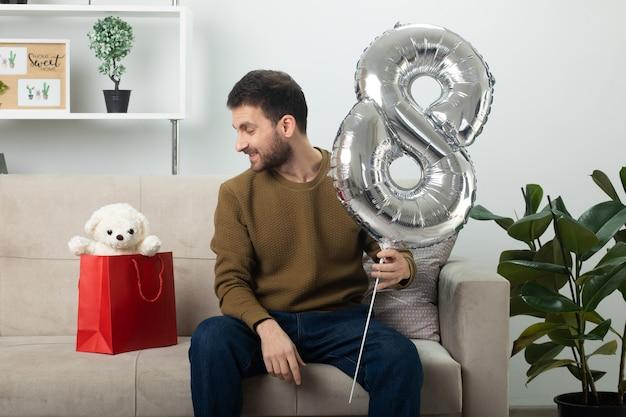 Uśmiechnięty przystojny mężczyzna trzymający balon w kształcie ósemki i patrzący na misia w torbie na prezenty siedzący na kanapie w salonie w marcowy międzynarodowy dzień kobiet