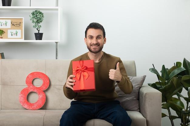 Uśmiechnięty przystojny mężczyzna trzymający czerwone pudełko i trzymający kciuki, siedzący na kanapie w salonie w marcowy międzynarodowy dzień kobiet