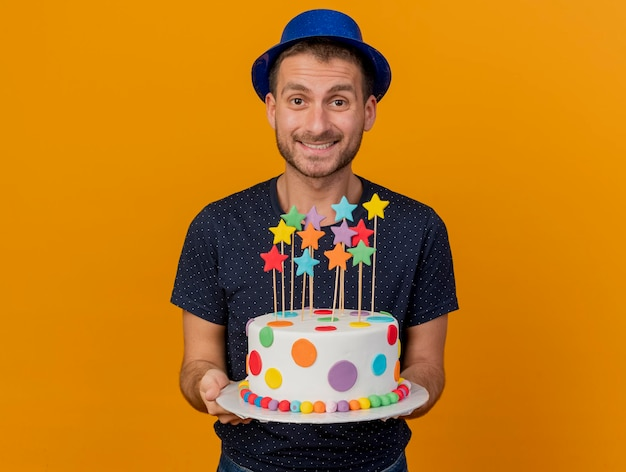 Uśmiechnięty przystojny mężczyzna ubrany w niebieski kapelusz strony posiada tort urodzinowy na białym tle na pomarańczowej ścianie z miejsca na kopię