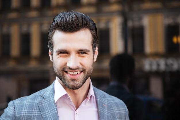 Uśmiechnięty przystojny mężczyzna w kurtki pozować
