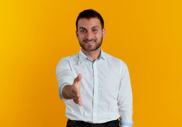 Uśmiechnięty przystojny mężczyzna wyciąga rękę na białym tle na pomarańczowej ścianie