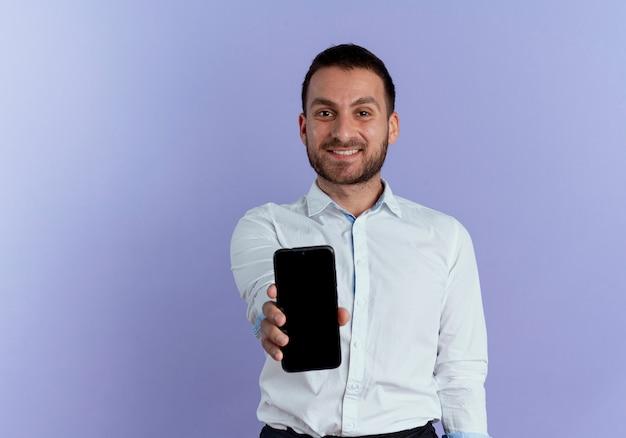 Uśmiechnięty przystojny mężczyzna wyciąga telefon na białym tle na fioletowej ścianie