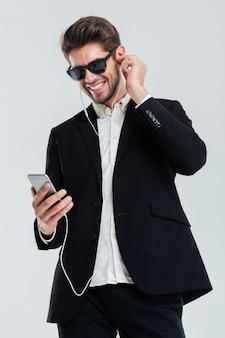 Uśmiechnięty przystojny młody biznesmen słucha muzyki przez słuchawki trzymając smartfon nad szarą ścianą