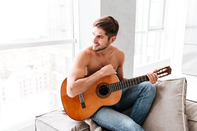 Uśmiechnięty przystojny młody człowiek siedzi i gra na gitarze w domu