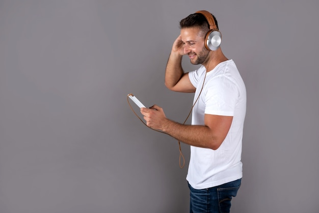 Uśmiechnięty przystojny młody człowiek w białej koszuli, słuchając muzyki na słuchawkach i trzymając smartfon, stojąc na szaro