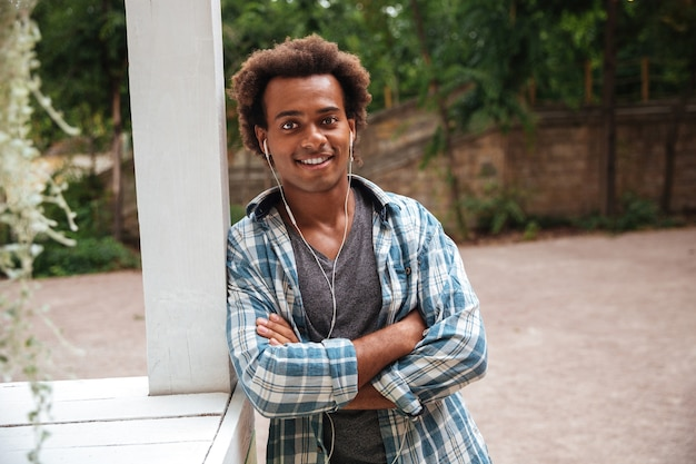 Uśmiechnięty przystojny młody człowiek w słuchawkach stojący z rękami skrzyżowanymi