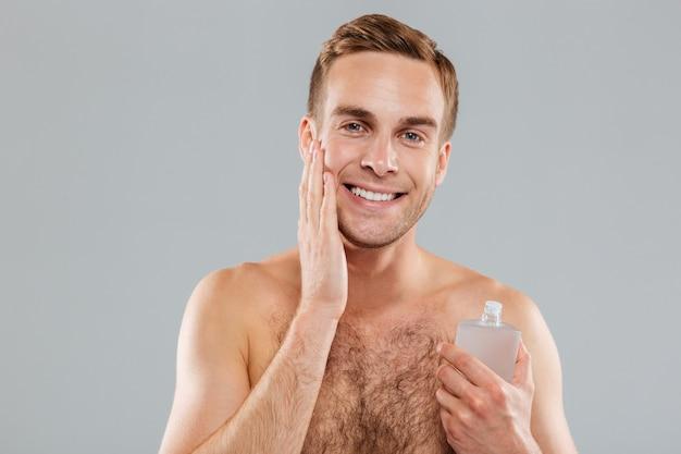 Uśmiechnięty przystojny młody mężczyzna nakłada balsam po goleniu na twarz nad szarą ścianą