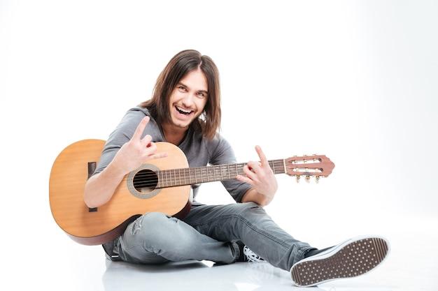 Uśmiechnięty przystojny młody mężczyzna siedzący na gitarze i wykonujący rockowy gest na białym tle