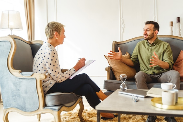 Uśmiechnięty przystojny młody mężczyzna w zwykłych ubraniach siedzący na kanapie podczas sesji terapeutycznej