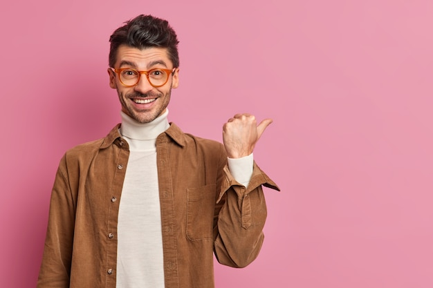 Uśmiechnięty przystojny młody mężczyzna wskazuje kierunek i wskazuje coś dobrego, pokazując miejsce na kopię reklamy