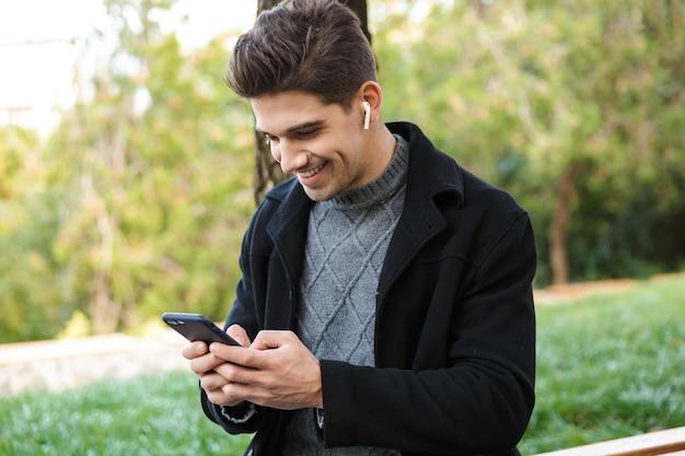 Uśmiechnięty przystojny młody wesoły mężczyzna w odzieży casual spaceru na świeżym powietrzu w zielonym parku przy użyciu telefonu komórkowego słuchania muzyki ze słuchawkami.