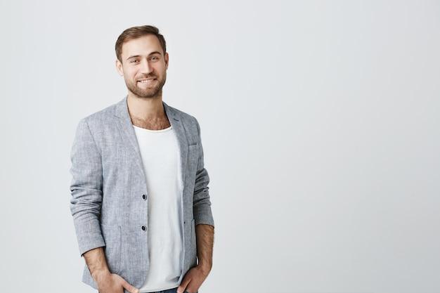 Uśmiechnięty przystojny przedsiębiorca patrząc na kamery