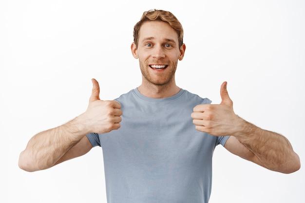 Uśmiechnięty przystojny rudy mężczyzna pokazując kciuk w górę z aprobatą, lubi i zgadza się, chwali i poleca ofertę promocyjną, zadowolony z czegoś, stojąc nad białą ścianą