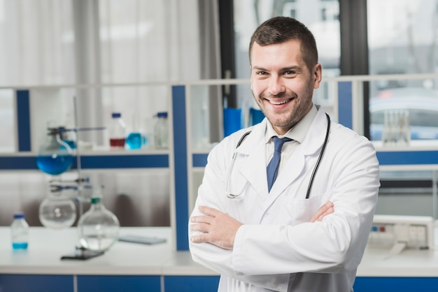 Uśmiechnięty przystojny student medycyny z rękami krzyżować