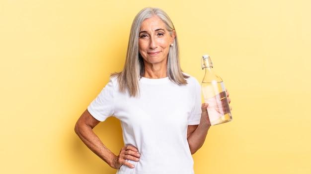 Uśmiechnięty radośnie z ręką na biodrze i pewny siebie, pozytywny, dumny i przyjazny i trzymający butelkę wody