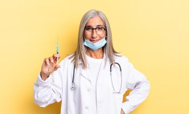 Uśmiechnięty radośnie z ręką na biodrze i pewny siebie, pozytywny, dumny i przyjazny. koncepcja lekarza i szczepionki