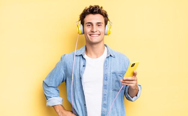 Uśmiechnięty radośnie z ręką na biodrze i pewny siebie, pozytywny, dumny i przyjazny. koncepcja słuchawek i smartfona