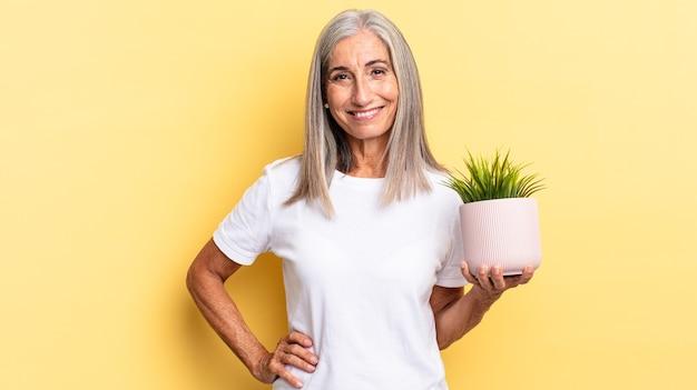 Uśmiechnięty radośnie z ręką na biodrze i pewny siebie, pozytywny, dumny i przyjazny, trzymający roślinę ozdobną