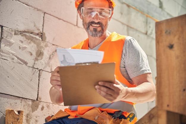 Uśmiechnięty, radosny inżynier budownictwa w okularach ochronnych, patrzący na projekt domu w dłoniach